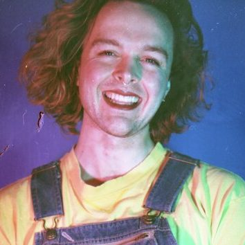 JB Bergin is sitting against a purple backdrop with their legs crossed, wearing denim overalls and a yellow shirt. They are a white person with shoulder length curly brown hair and are wearing lipstick. They are smiling widely at the camera.