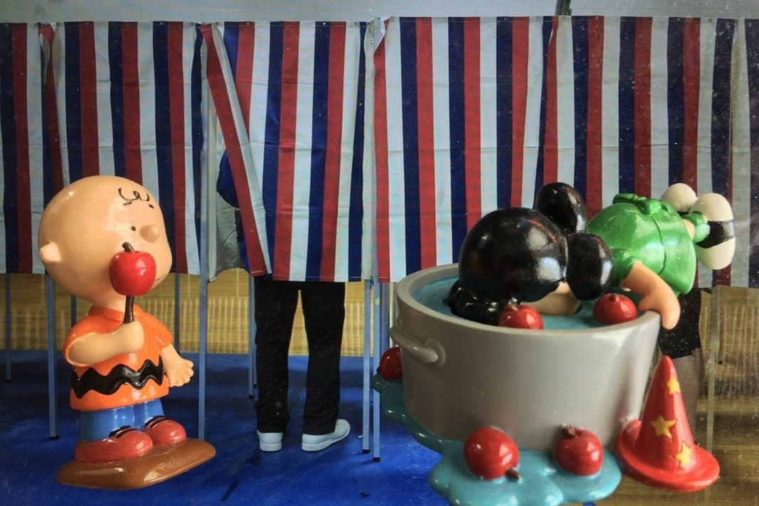 Before red, white, and blue polling booths, images of Peanuts characters are superimposed to appear life-sized. Charlie Brown holds an apple on a stick, while Lucy van Pelt bobs for hers in a bucket of water.