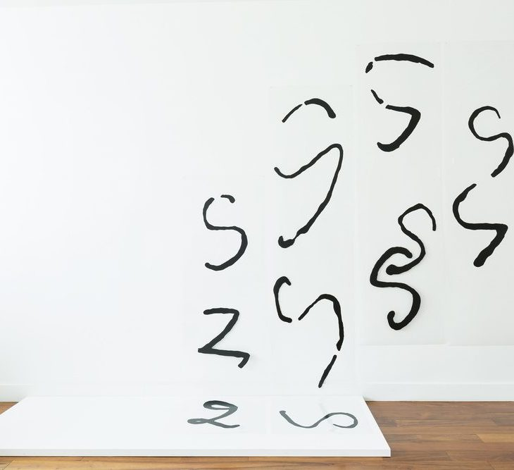 """Acrylic, handwritten iterations of the letter """"S"""" and """"Z"""" meander from a white panel on the ground up onto a white wall, some in broken into parts, others in thick, globby lines."""