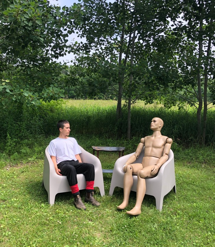 two seated bodies- one human, one mannequin, in chairs with a table in a field
