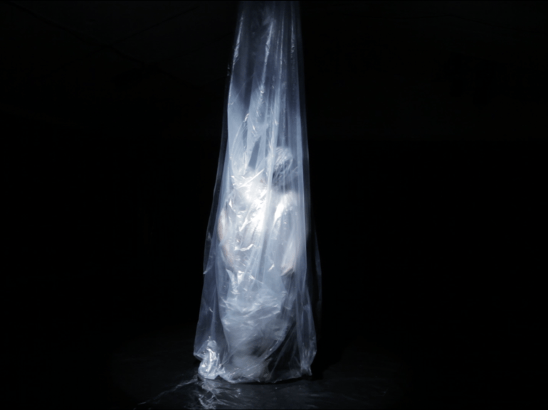 Cradled in plastic cocoon, a person is suspended upright, slumped onto their knees, naked and vulnerable like a fetus in the womb.