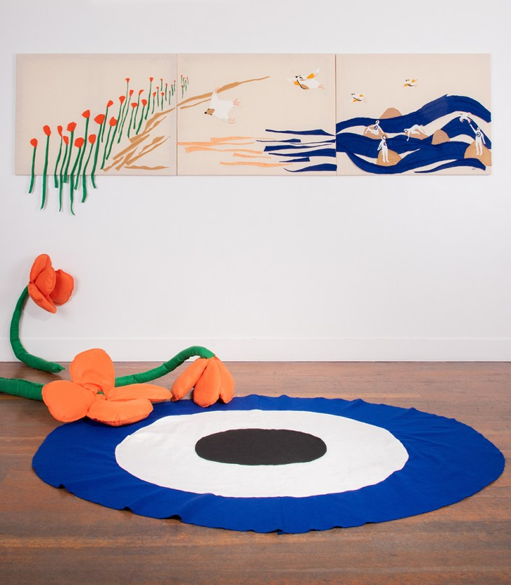Installation view of Bonny Nahmias's work. A long, horizontal image made of felt hangs on the wall. There are orange poppies flowing into a seascape with humanoid figures in the waves. Three enormous felt poppies droop along the wall and on the floor, where there is a circular felt rug that resembles a mati.