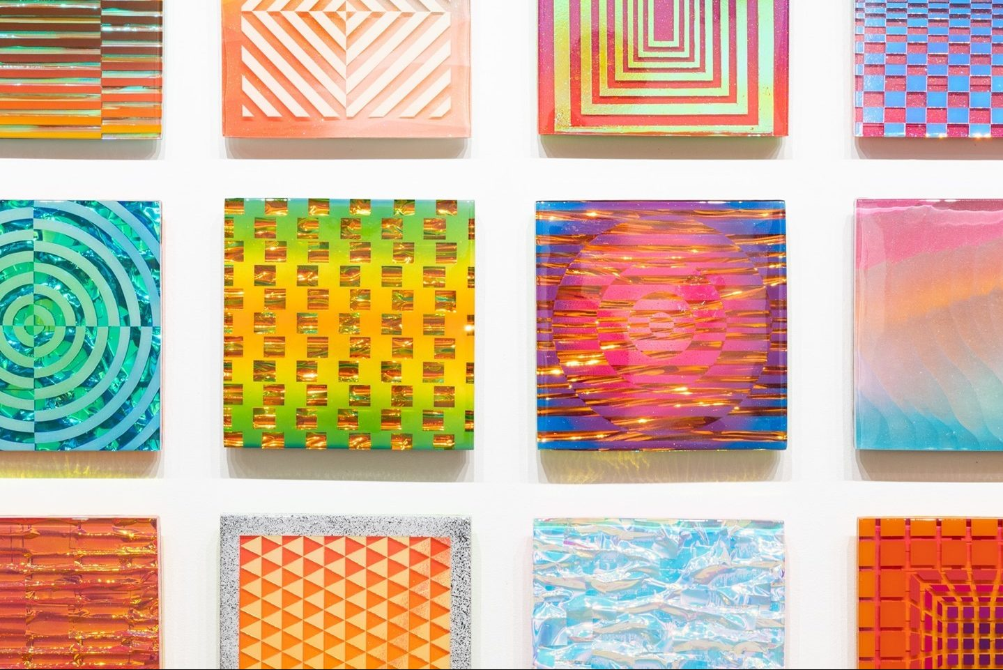 Arranged in perfect rows, these dazzling square pieces glitter against their white wall and tantalize, like a glossy, unwrapped hard candy, with their patterns, colors, and trick of the eye.