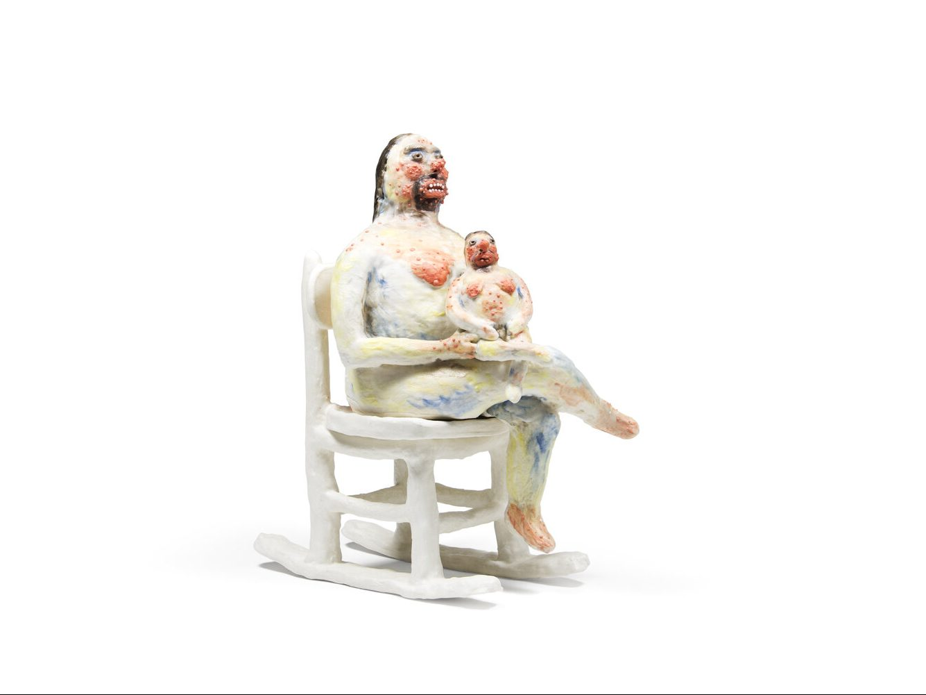 A woman sits in a rocking chair with her legs crosse and a child seated on her lap. They are both crudely sculpted out of a milky material, painted in a cloud of bright colors, and gazing into the distance blankly.