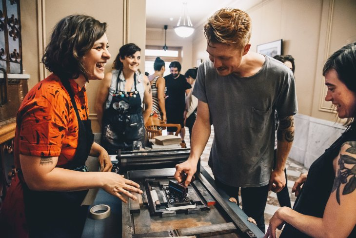 A woman wearing an apron laughs while a man rolls link onto blocks on a letterpress. Various folks look on, while numeros others mingle in the background.