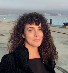 Leora Fridman on a waterfront in Richmond, MA. She is a light skinned woman in her thirties with medium length curly brown hair, brown eyes, and nose ring. She's smiling at the camera.