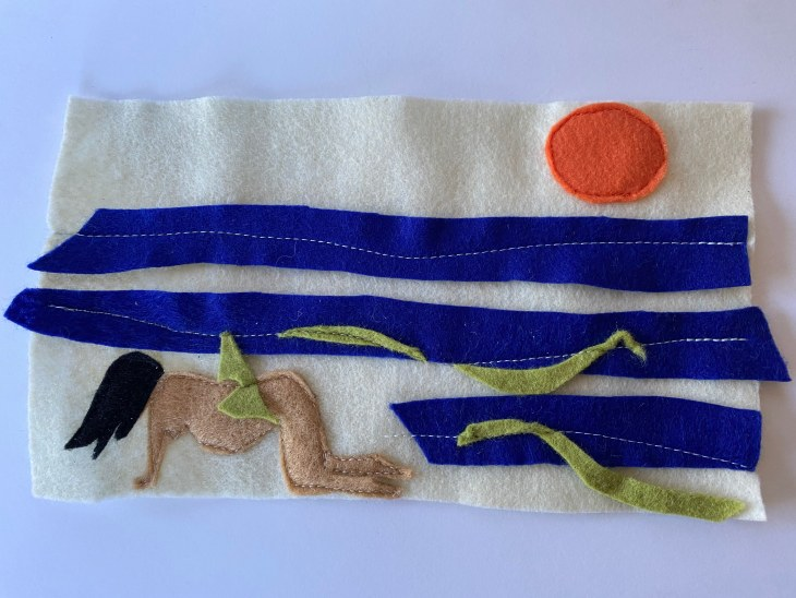 A rectangular image made in felt pieces. Long, horizontal scraps in deep blue create an ocean horizon, above which a deep orange sun sits. In the bottom left corner, a nude, pregnant woman is on all fours with her hair covering her face.