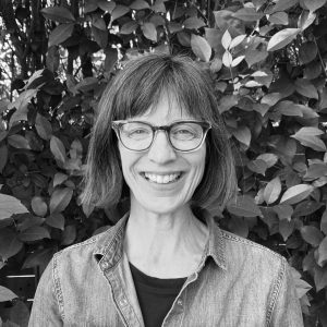 Tanya Ward Goodman is standing in front of a tall hedge. She is a woman in her fifties with medium skin tone, brown, bobbed hair and glasses. She wears a denim shirt and is smiling with all her teeth.