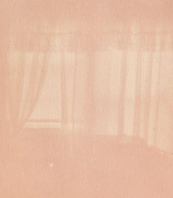 In monochromatic, soft pink hues, curtains that drape over a corner window haunt the background of this extremely faded and washed photograph.