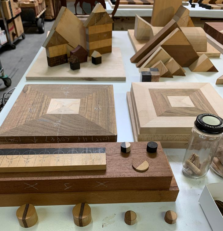 Pieces of treated, in-progress wood are organized on a white table and marked in pencil. Behind those in the foreground are triangular pieces, those in the shapes of small houses, so on; and beyond that, glances of a studio space.