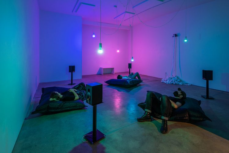 In a room draped with a warm amalgamation of blue, magenta, and pink light, three individuals lie on their backs on large, black pillows. Speakers stand on short pedestals and on the far wall, paper spills from an installation piece onto a pile the ground.