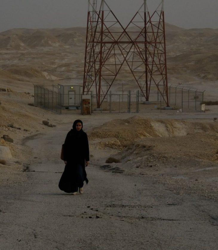 A woman in all black walks toward the camera, a vast desert landscape stretching behind her toward lumpy, hilly horizon. An tower stands just over the bend in the road behind her. She wears white shoes.