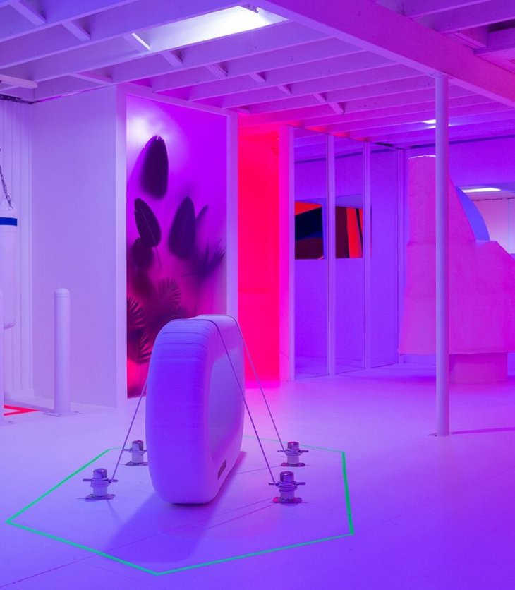 Purple and pink light fills a a room with white walls, ceiling, and floor. Two translucent walls have large plants pressed against them, backlit by green, purple, and pink lights. There is a large, white, inflated oval in the center of the room, anchored to the floor by ropes.