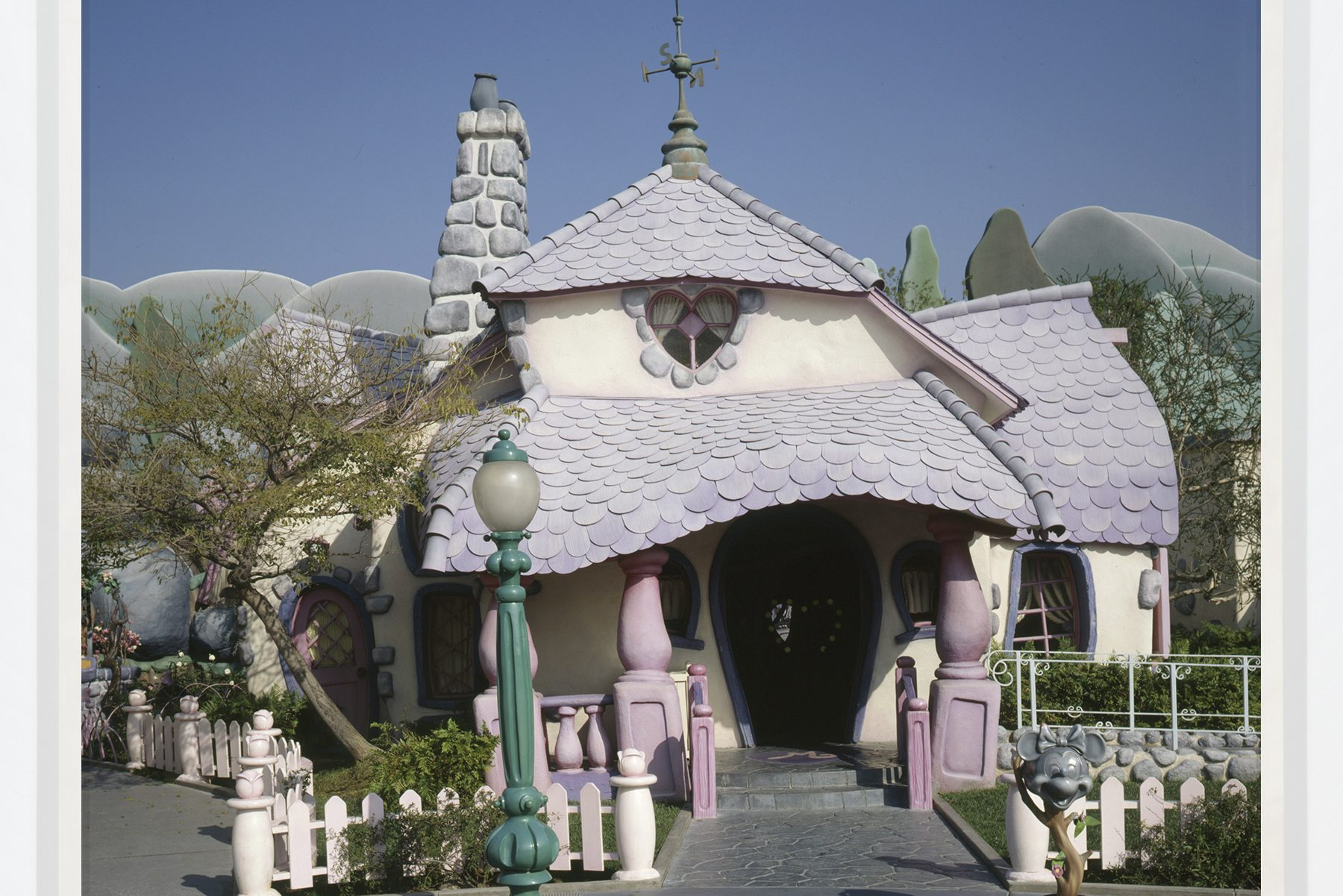 A cartoonish house, with a stone chimney and imbricated pink tiles, squats, blubbery and soft against a similarly cartoonish backdrop of rolling, grey hills.
