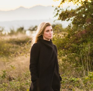 Emily Tanner-McLean is standing in a field in Discovery Park, Seattle. She is a light skinned woman in her thirties with long blond hair and wears a black coat. She looks off to the side, lost in thought.