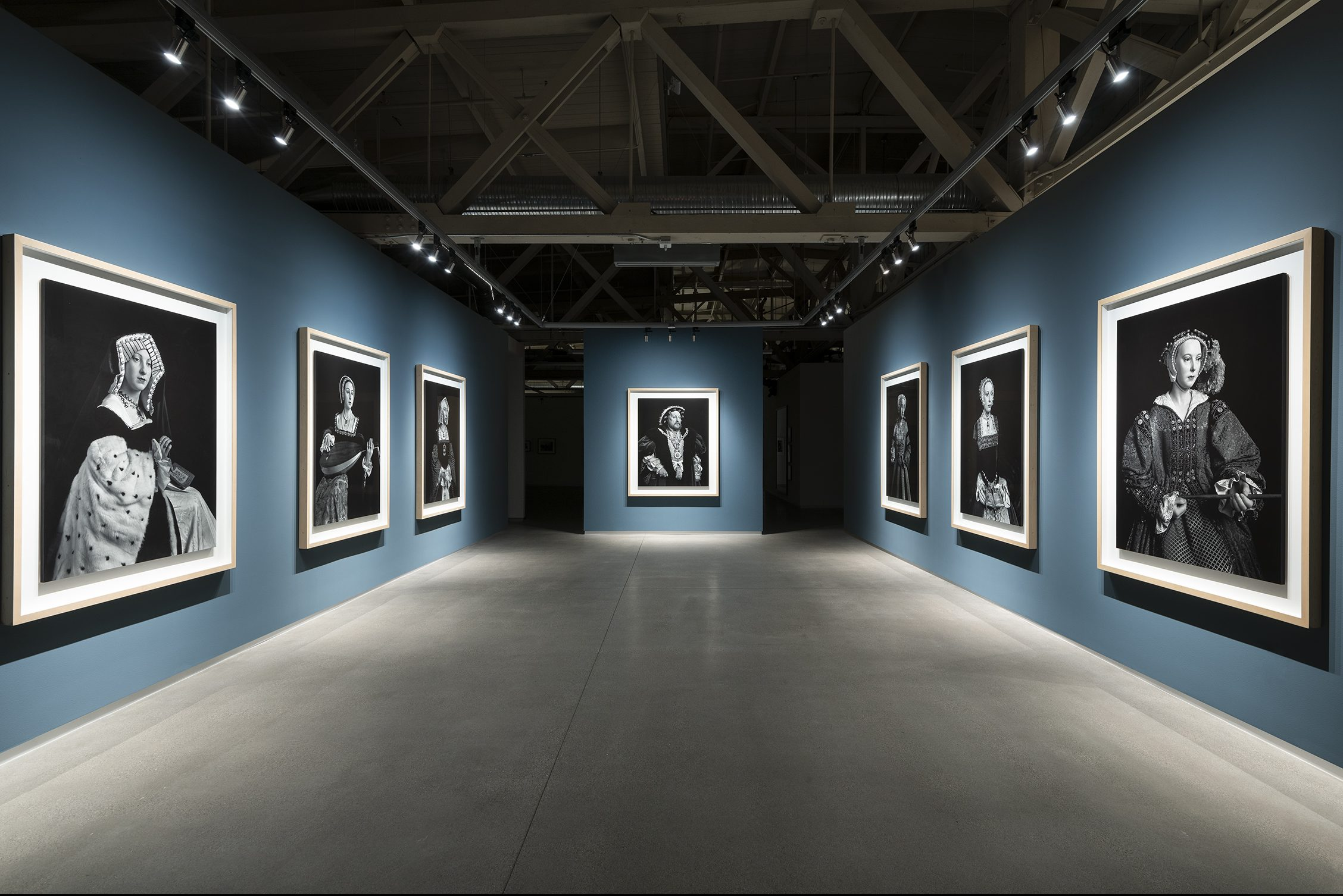 Seven black and white images hand on the blue walls of a narrowing gallery space, each equally sized with one in the far, center wall. All seem to be portraits of renaissance-era figures.