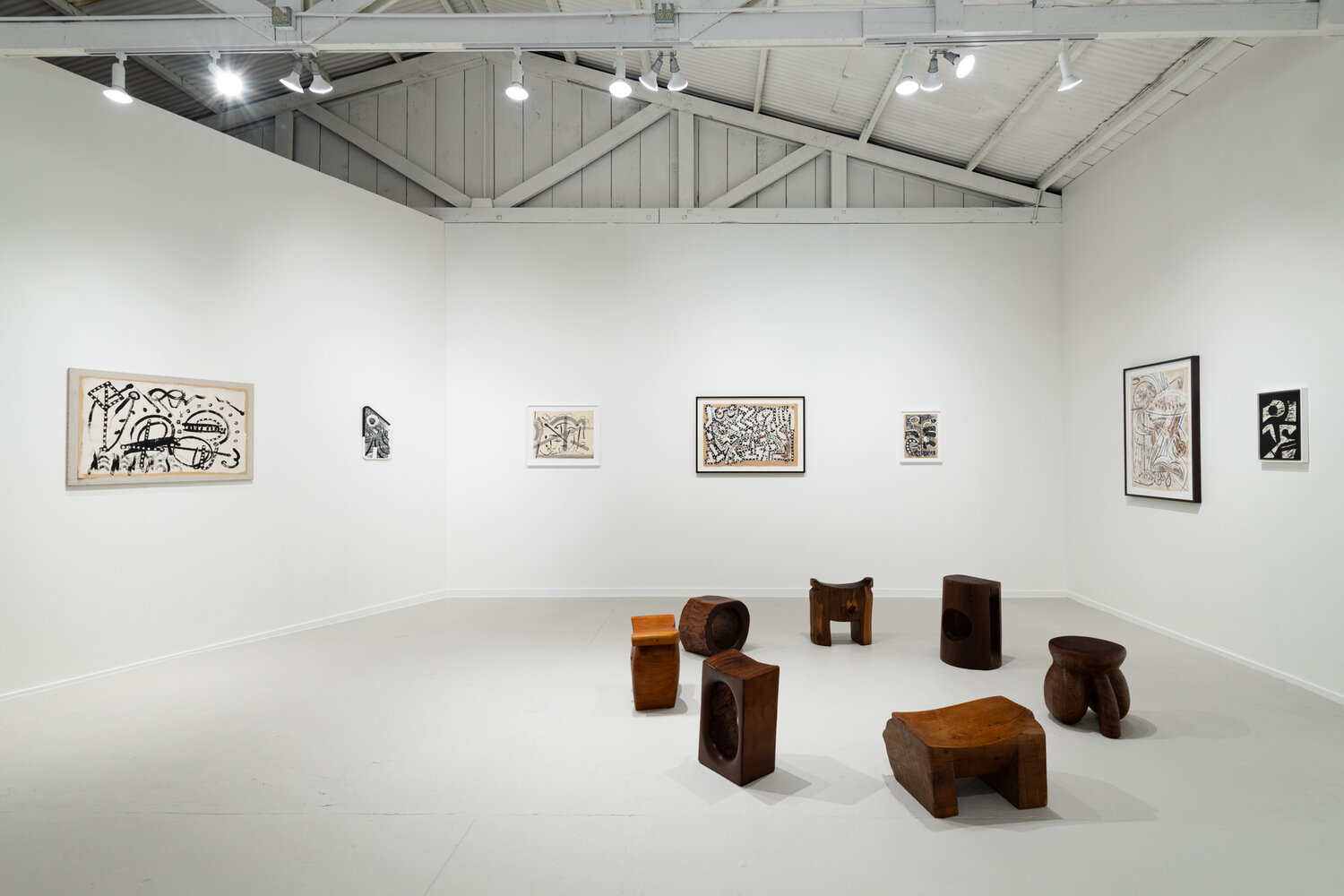 In a circle on a white floor, seven carved wooden sculptures of different shapes and sizes are arranged. Some rectangular, some cylindrical, some squatting, some more upright. On the white walls behind these, seven pieces of art hang on the walls.