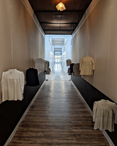 Antebellum shirts with beaded seams and ironed collars of numerous colors float ominously along the wall of a gallery space hallway at torso height.