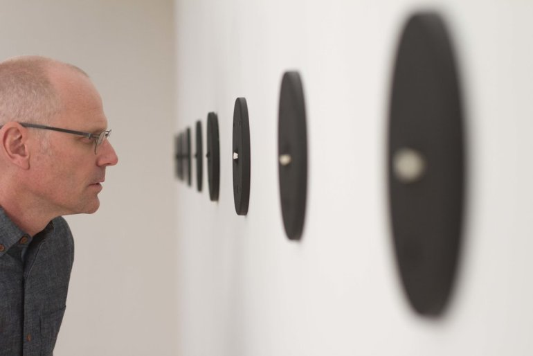 A tight shot of an individual wearing glasses and gazing into one of the eyeball wall fixtures mounted on the wall in a row. The rest of the gallery space is blurred.