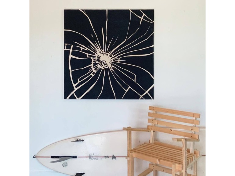 A square painting, dominated by the converging white lines of shattered glass, hangs above a wooden chair and a white surfboard, leaning against the wall on its side.