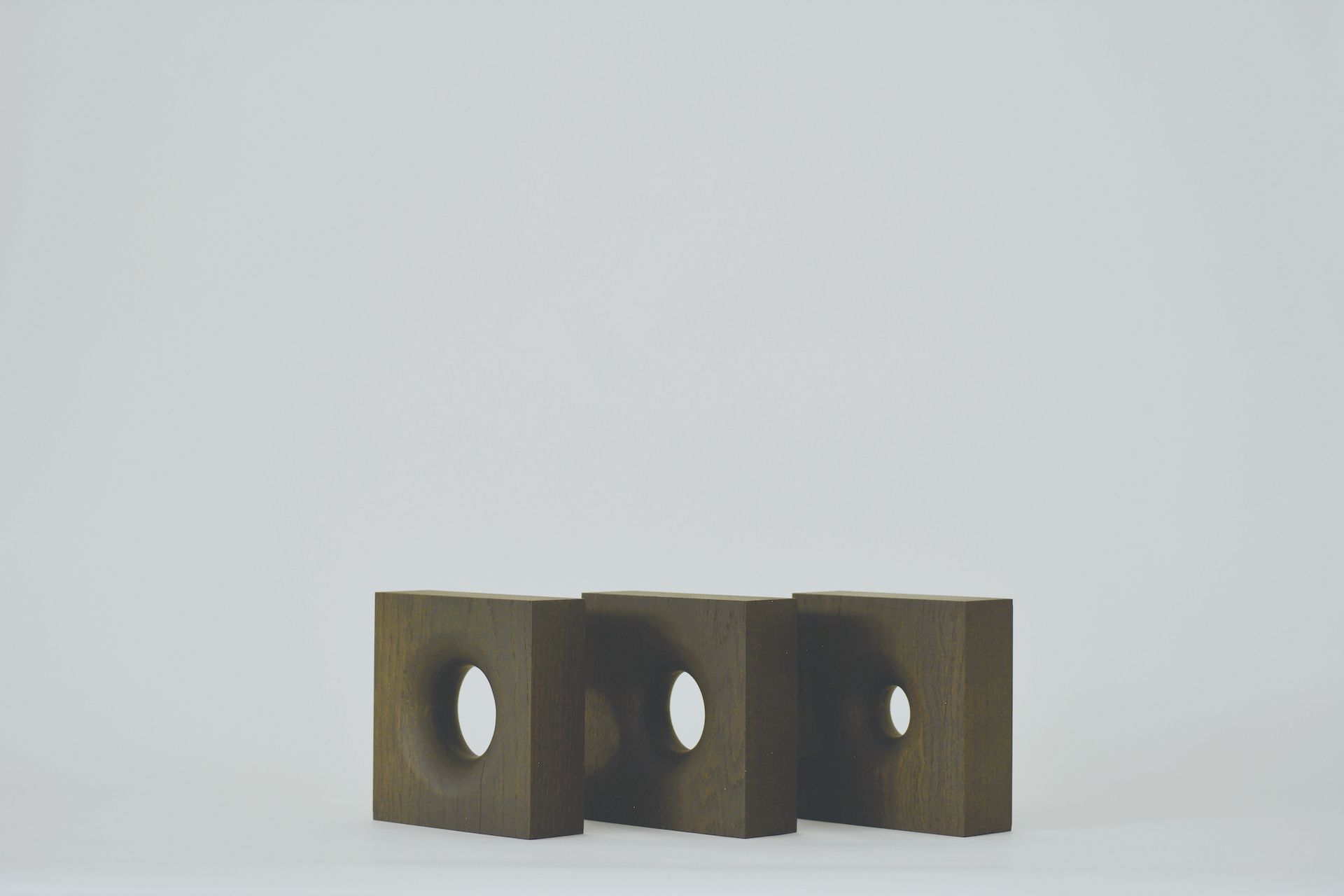Three square blocks are lined up in a row, each with a smoothed hole in the center that decrease in size with each cube, all against a hazy white background.