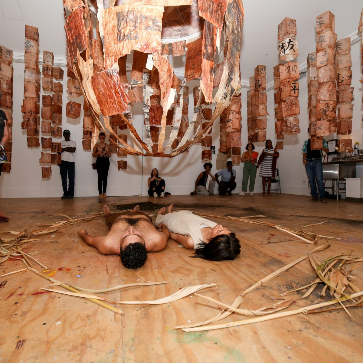 In the center of a room, two individuals lie on the ground, their gaze fixed on a massive sculpture, recalling the shape of an atomic bomb, which is hovering just above them. Around the edge of the room, people watch a chilling moment unfold; among them, more vertically hanging sculpture hang.