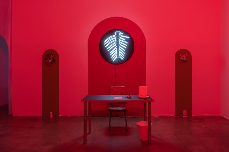 A low-lit room is drenched in red, a desk and small chair centered beneath a blue, neon light the shape of something like an animal spine, and two grey columns that climb halfway up the wall, adorned with animal masks.