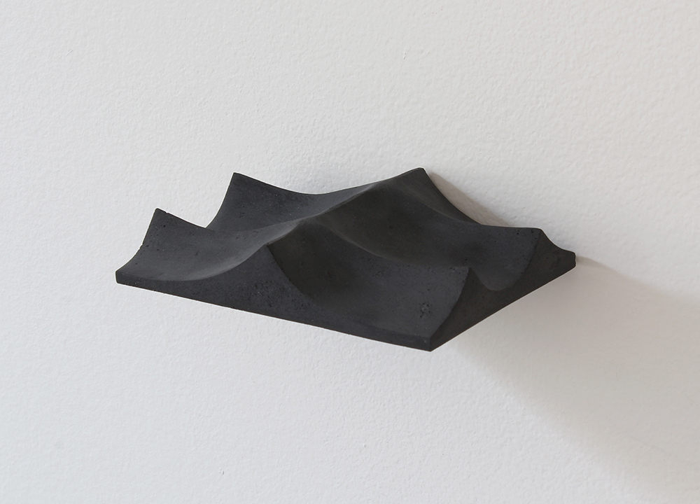 A black object hanging against a white wall resembles undulating mountains, or waves in the ocean, with sharp peaks and smoothed valleys.