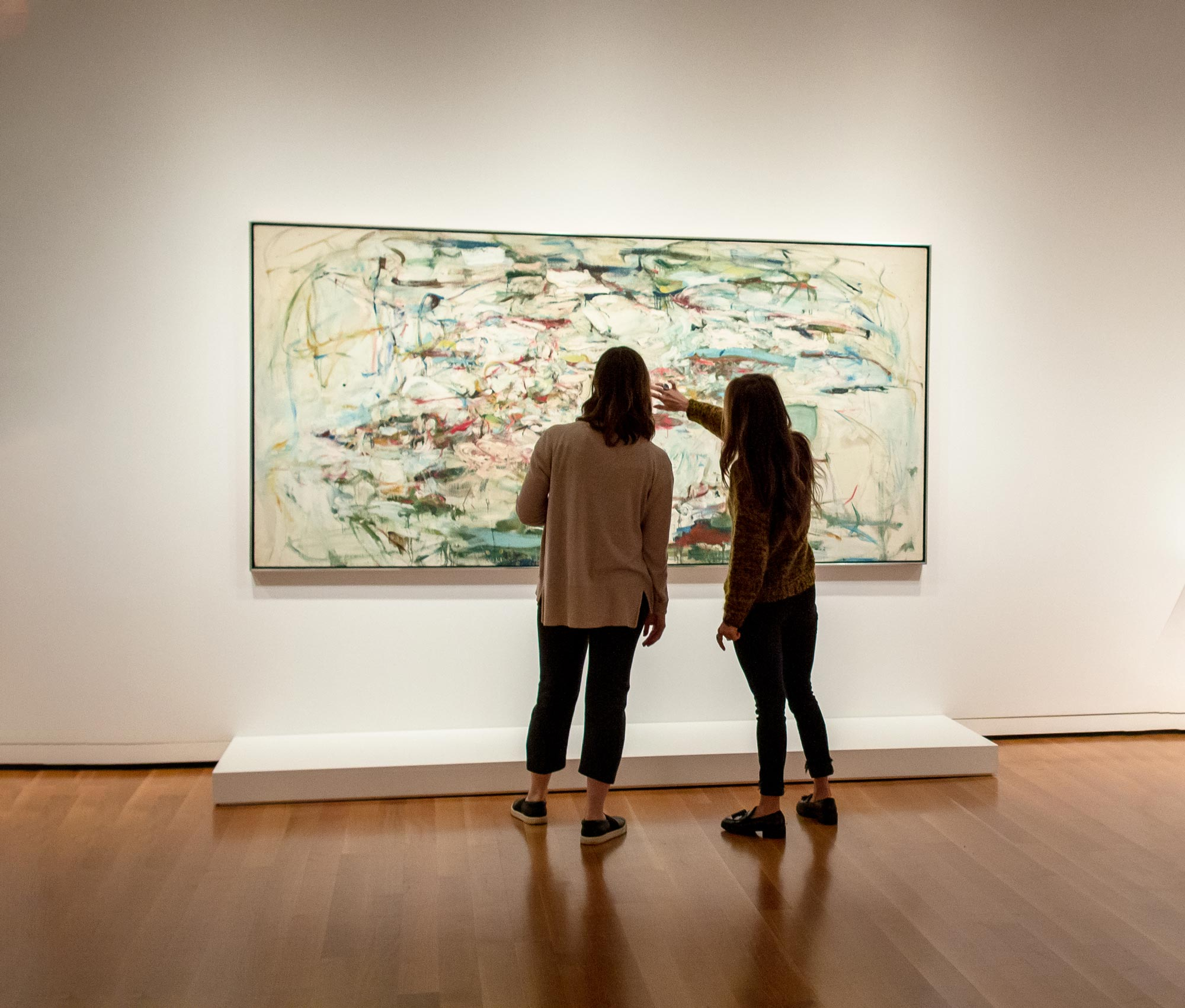 Two individuals stand before a large, abstract painting hanging on a white wall and above warm, wooden floors. One of the two points toward the center, which crackles with color and motion and mood.