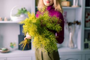 young florist girl with a big bouquet of mimosa in hands.