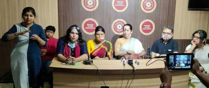 This medium-shot photograph shows a scene from the release of the 'Bengal Trans* & Queer Charter of Demands' at the Press Club Kolkata on March 27, 2021. To the extreme left is sign language interpreter Rajani Banerjee. Beside her are the LGBTIQA+ speakers for the media conference. Seated from left to right are Rahul Mitra, Raina Roy (speaking into a microphone), Tista Das, Aparna Banerjee, Pawan Dhall (moderator), and Sudeb Suvana. A tablet held up by a member of the audience to record the media conference proceedings can be seen at the right edge of the photograph. The wall behind the speakers is covered with wooden panelling and has the Press Club Kolkata logo pasted on the wall. Photo credit: Rafiquel Haque Dowjah