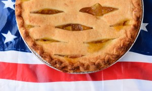 Apple Pie simply American! Overhead shot of a lattice top apple pie on an American Flag table cloth.