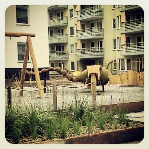 Trollslända av trä på innergård i Henriksdalshamnen