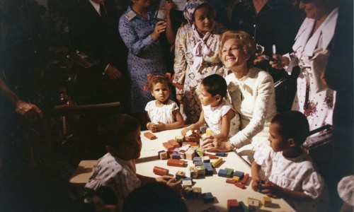 Pat Nixon smiles for the cameras as she plays with children at a school in Egypt.