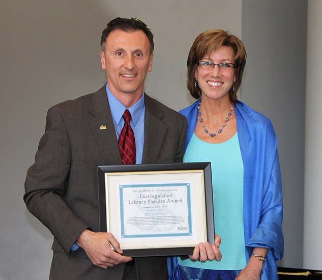 Robert Vay receives George Mason University Libraries' Distinguished Faculty Award from Associate Provost Kimberly Eby, April 2014.