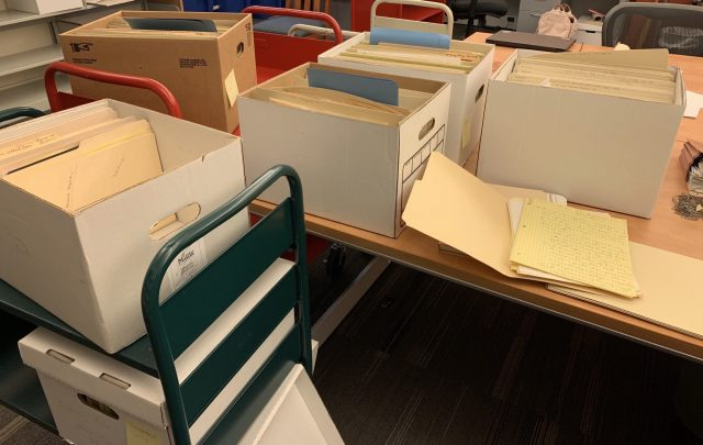 Three open boxes partially full of files. Two more open boxes are on a file cart.