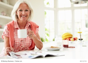 Middle Aged Woman Reading Magazine Over Breakfast