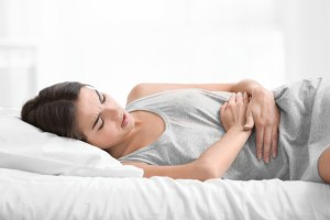 woman laying down experiencing severe menstrual pain