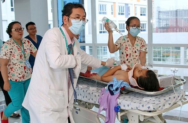 Bác sĩ Nguyễn Minh Tiến, Phó giám đốc Bệnh viện Nhi đồng Thành phố trực tiếp đẩy băng ca đưa bệnh nhân vào phòng cấp cứu sáng 20/9. Ảnh: Minh Gia.