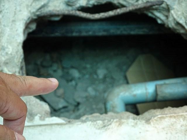 Hố sâu 40 cm trong mái hiên nhà ông Long. Ảnh: Hà An.