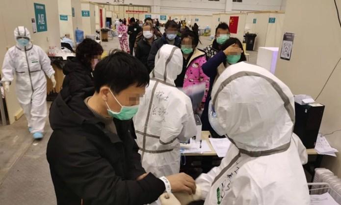 Nhân viên y tế làm thủ tục tiếp nhận bệnh nhân tại bệnh viện tạm thời ở Vũ Hán, tỉnh Hồ Bắc. Ảnh: Xinhua.