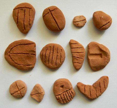 Sumerské počítacie žetóny. Žetón v ľavom dolnom rohu označuje ovcu alebo kozu (4. tisícročie pred n.l.).