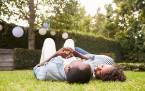 couple lying outside on the grass discussing safety of sex during covid