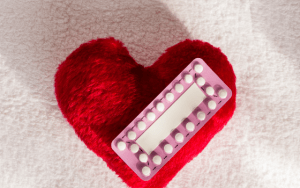 birth control pills on a red heart
