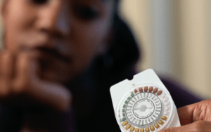 black woman holding a pack of birth control pills