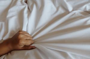 hand grasping white sheet
