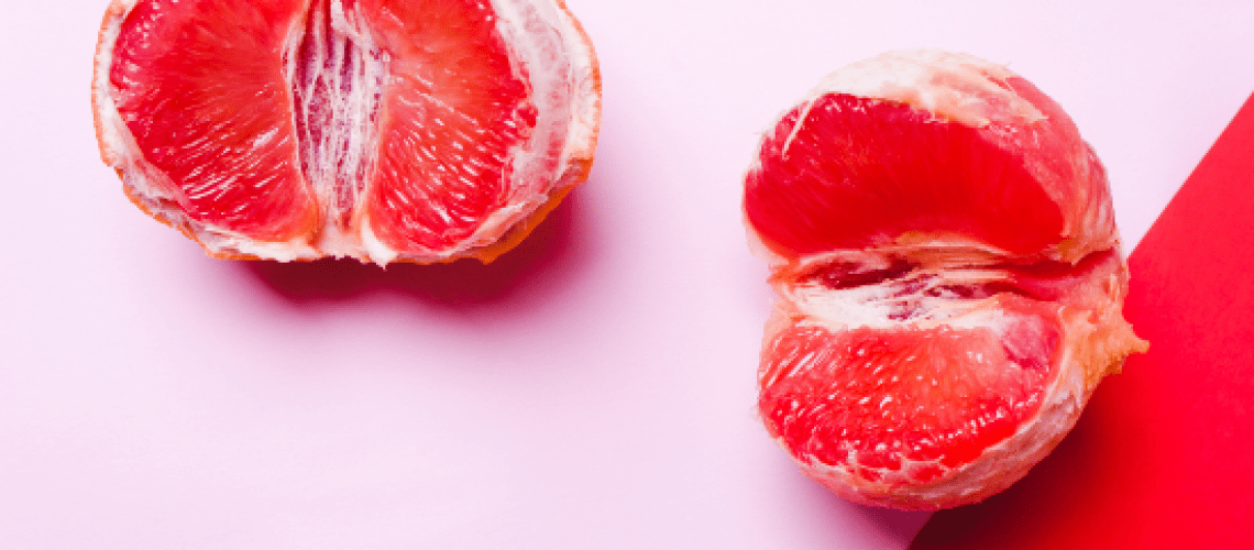 two grapefruits on a pink background representing an inflamed vulva