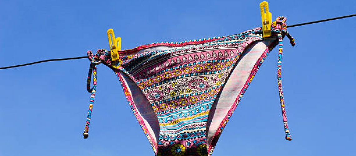Drying woman swimsuit against the blue sky