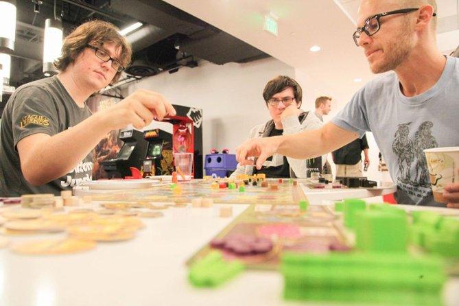Tres compañeros de trabajo varones jugando en un torneo de juego de mesa