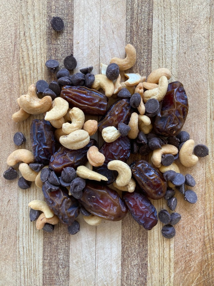 cashews dates and chocolate chips on wooden cutting board
